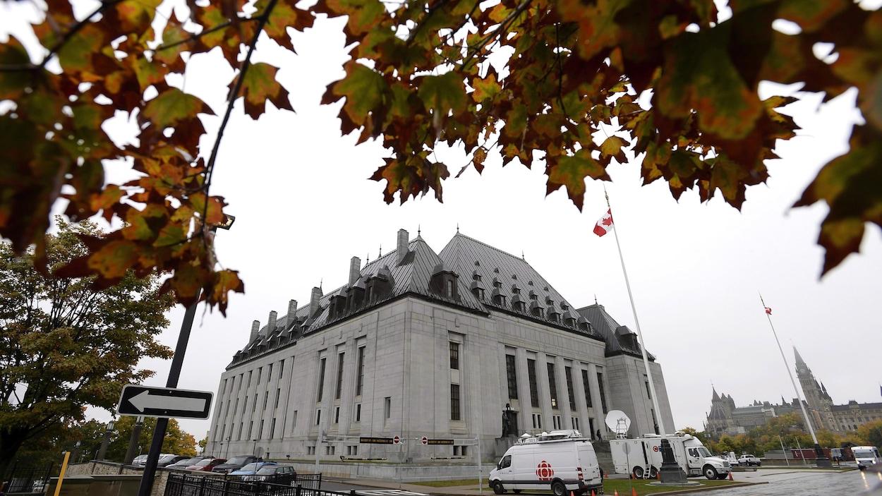 Façade de la Cour suprême du Canada entourée d'arbres pendant l'automne.