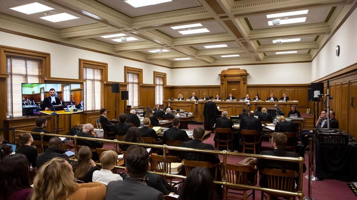 Les 9 juges de la Cour suprême siègent au fond d'une salle d'audience remplie d'avocats et de membres du public.