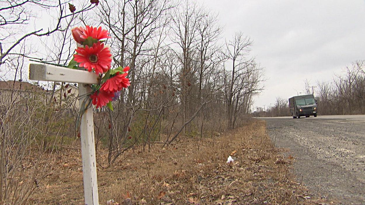 Une croix décorée de fleurs rouges posée en bordure d'une route.