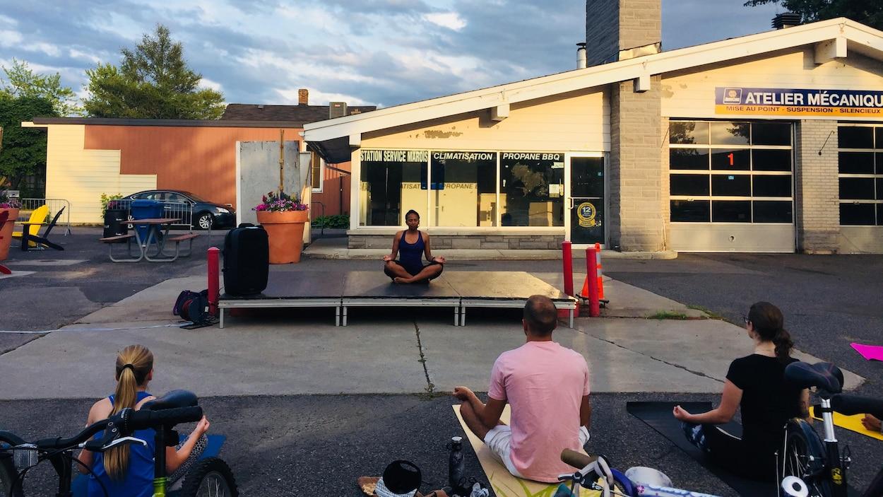 Une femme sur une plateforme enseigne le yoga en plein-air, devant la station-service désaffectée.