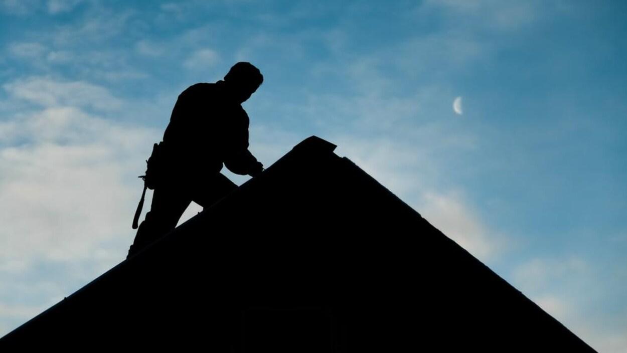 Un couvreur à contre-jour au sommet d'un toit.