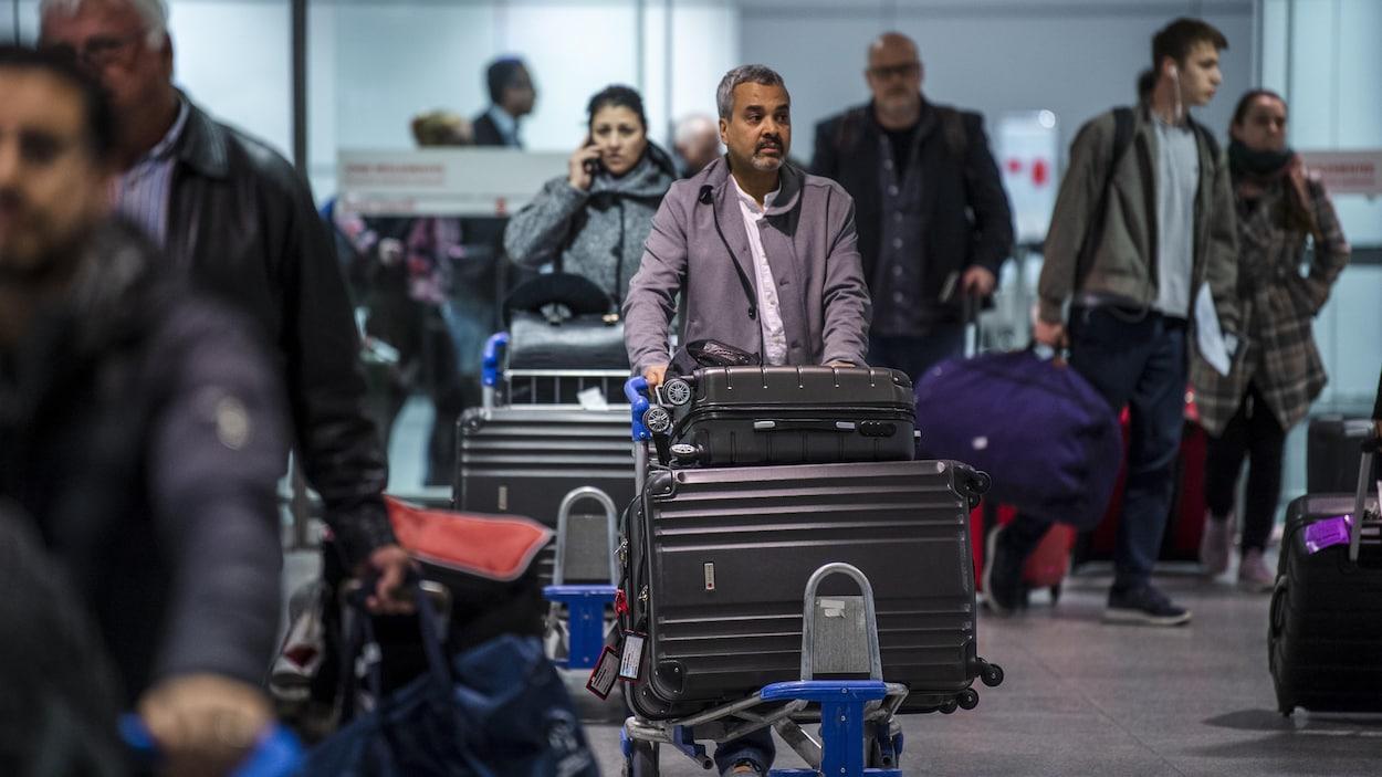 Des passagers entrent dans la zone d'arrivée à Montréal d'un vol d'Air Canada en provenance du Maroc.