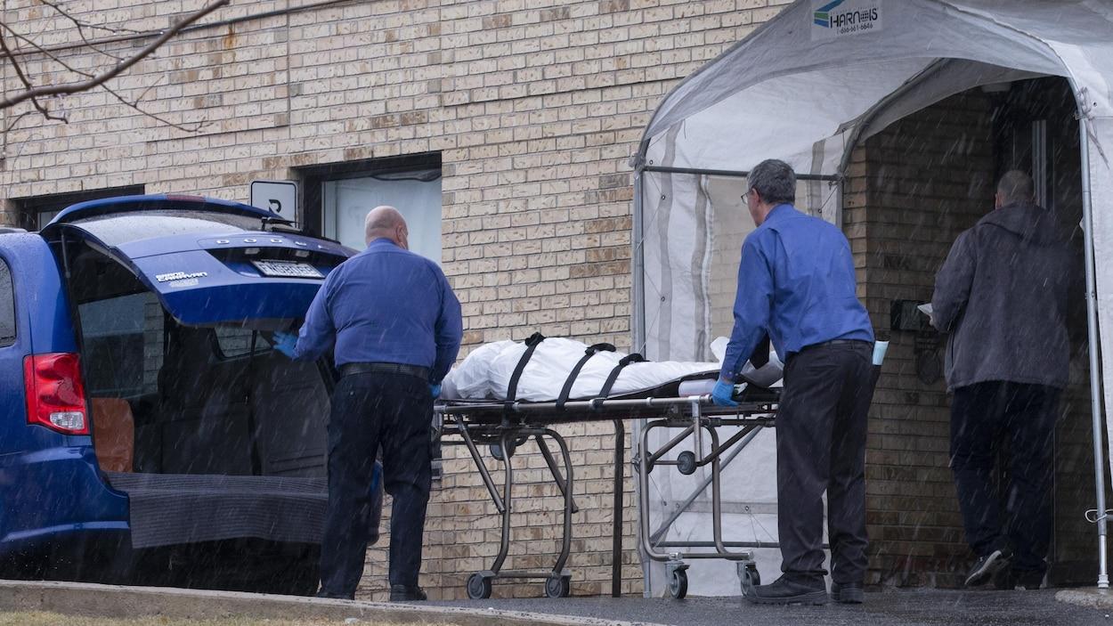 Deux employés d'un centre funéraire évacuent un cadavre d'un CHSLD.