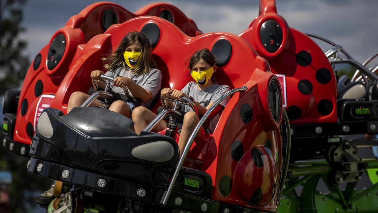 Deux jeunes filles portent un masque jaune dans un manège au parc d'amusement Playland à Vancouver.