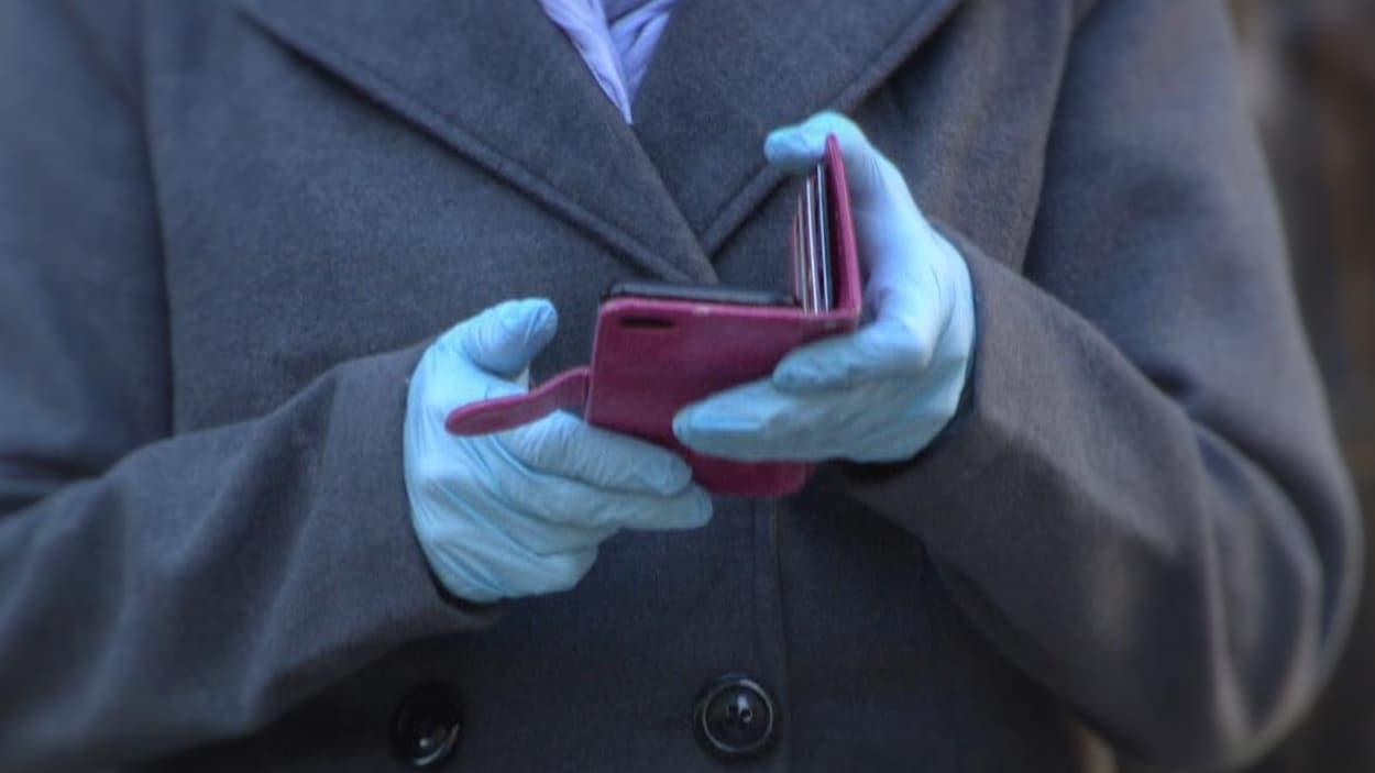Une personne consulte son téléphone cellulaire avec des gants.