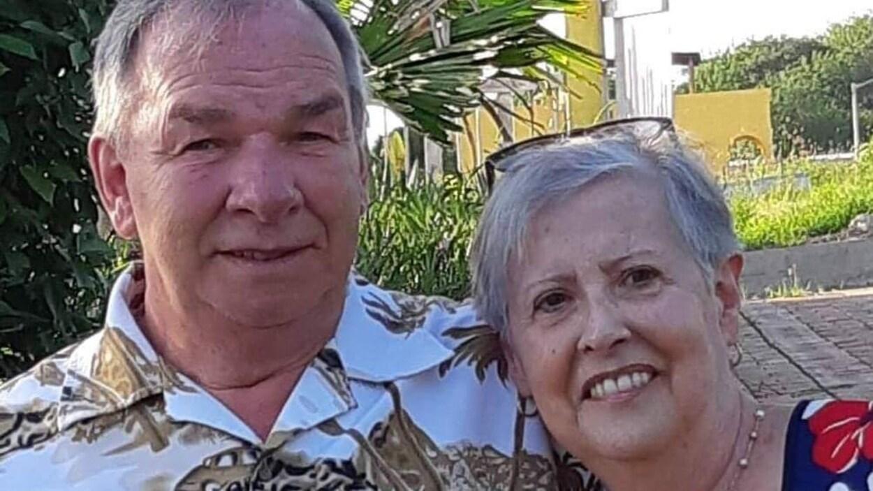 La photo d'un homme et d'une femme devant un palmier.