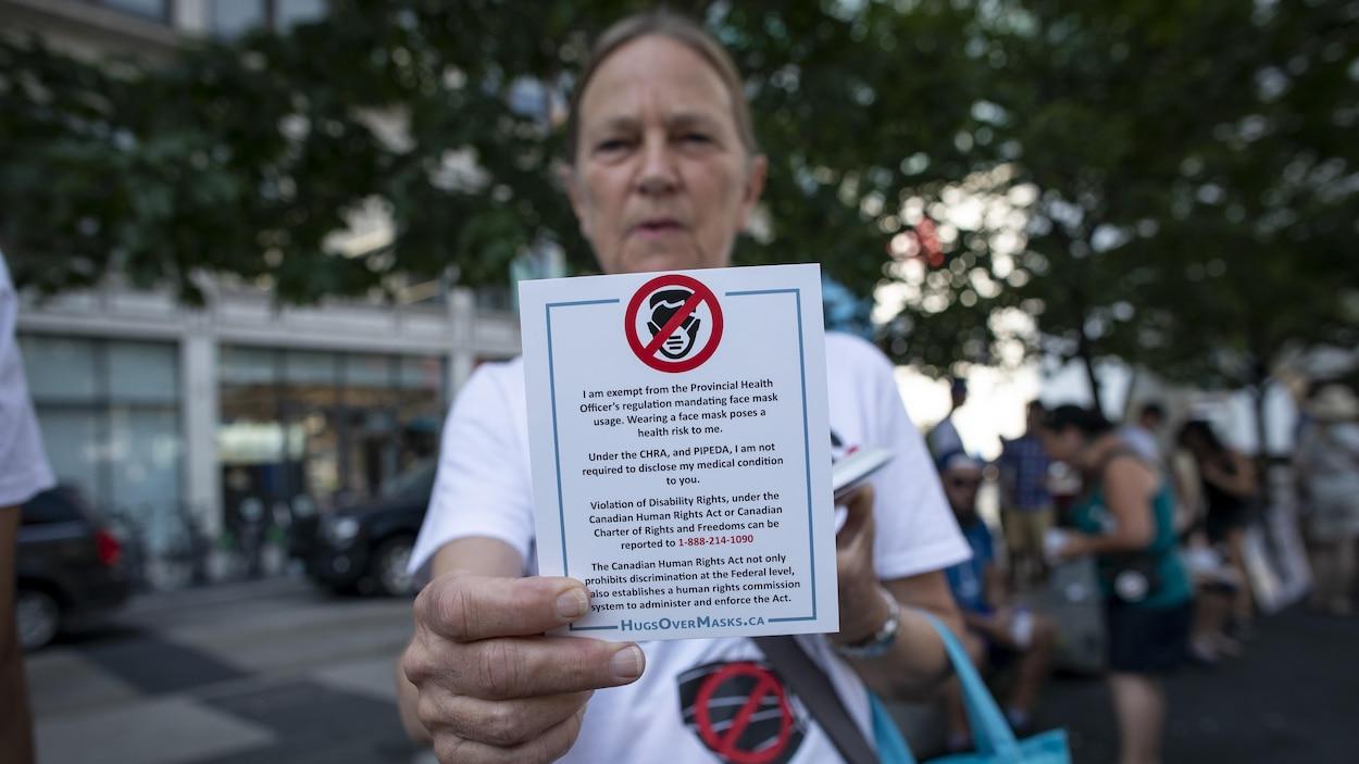 Une manifestante qui s'oppose au port du masque obligatoire à Toronto brandit une carte.