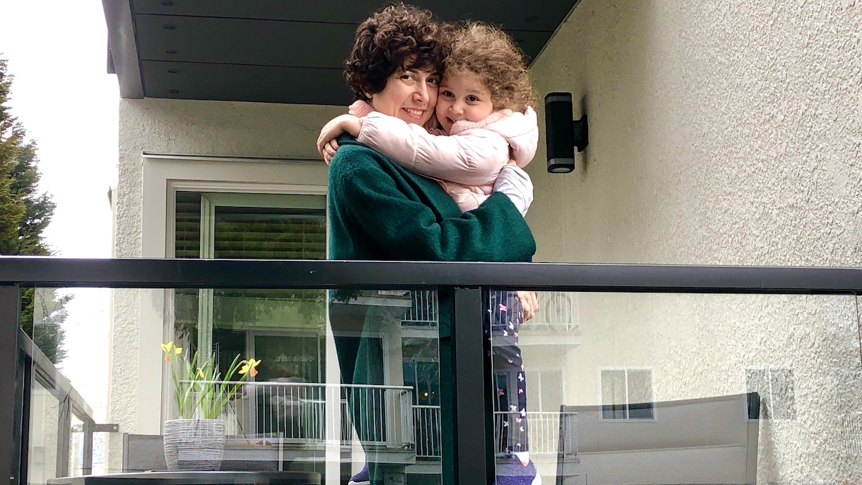 Ghinwa Yassine et sa fille Gia s'enlacent, debout sur leur balcon.