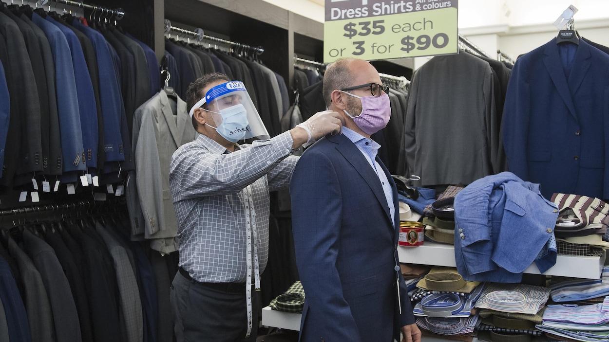 Un tailleur portant un masque mesure le cou d'un client portant lui aussi un masque.