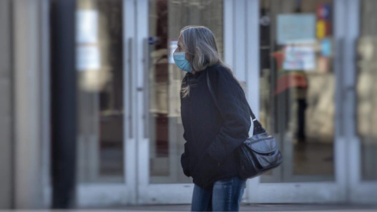 Une personne à l'extérieur avec un masque au visage.