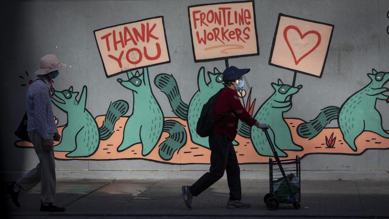 Deux femmes qui portent un masque passent devant une murale dédiée aux travailleurs essentiels.