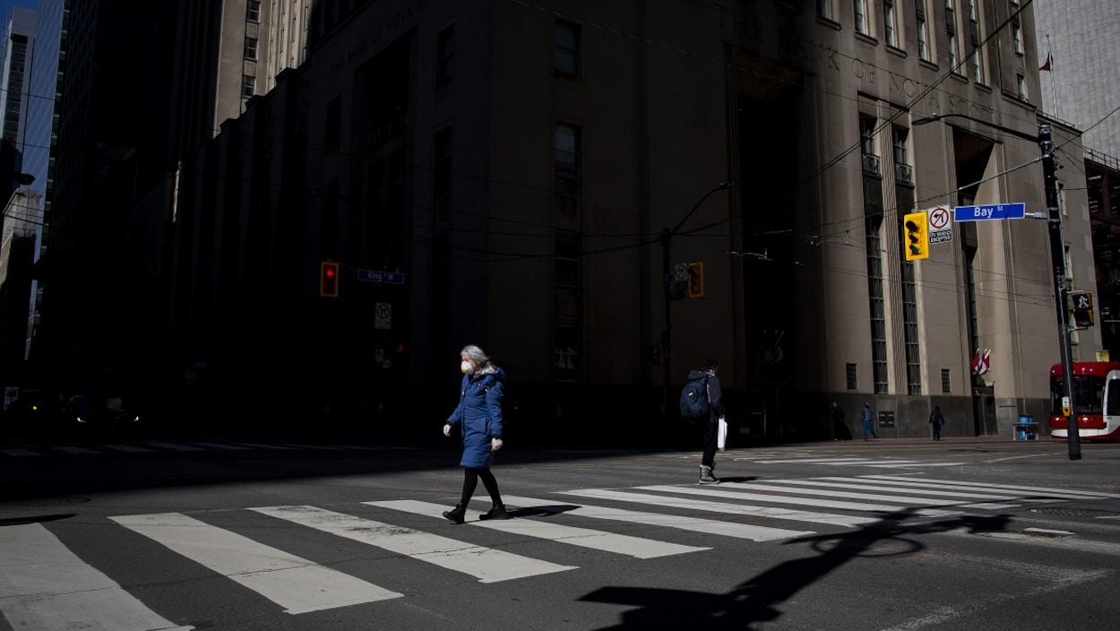 Une femme portant un masque de protection marche dans une rue du centre-ville de Toronto.