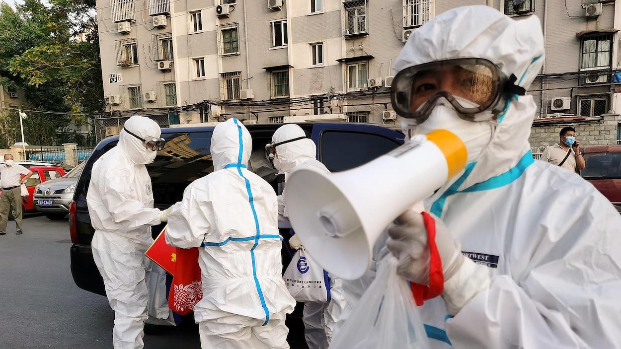 Du personnel en combinaison de protection dans la rue à Pékin, une personne parle dans un porte-voix.