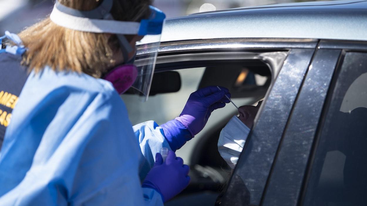 Une travailleuse de la santé en train d'insérer une tige dans le nez d'un homme pour un test de dépistage.