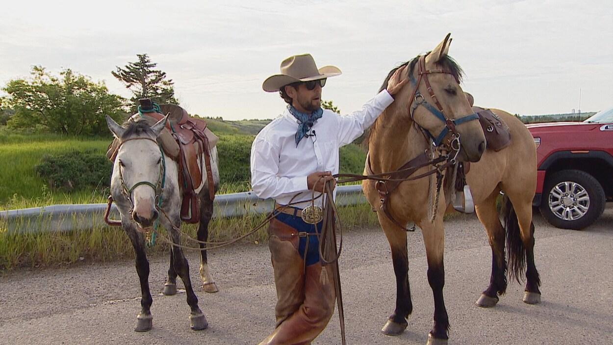 Filipe Masetti Leite à côté de ses deux chevaux habillé en cowboy.