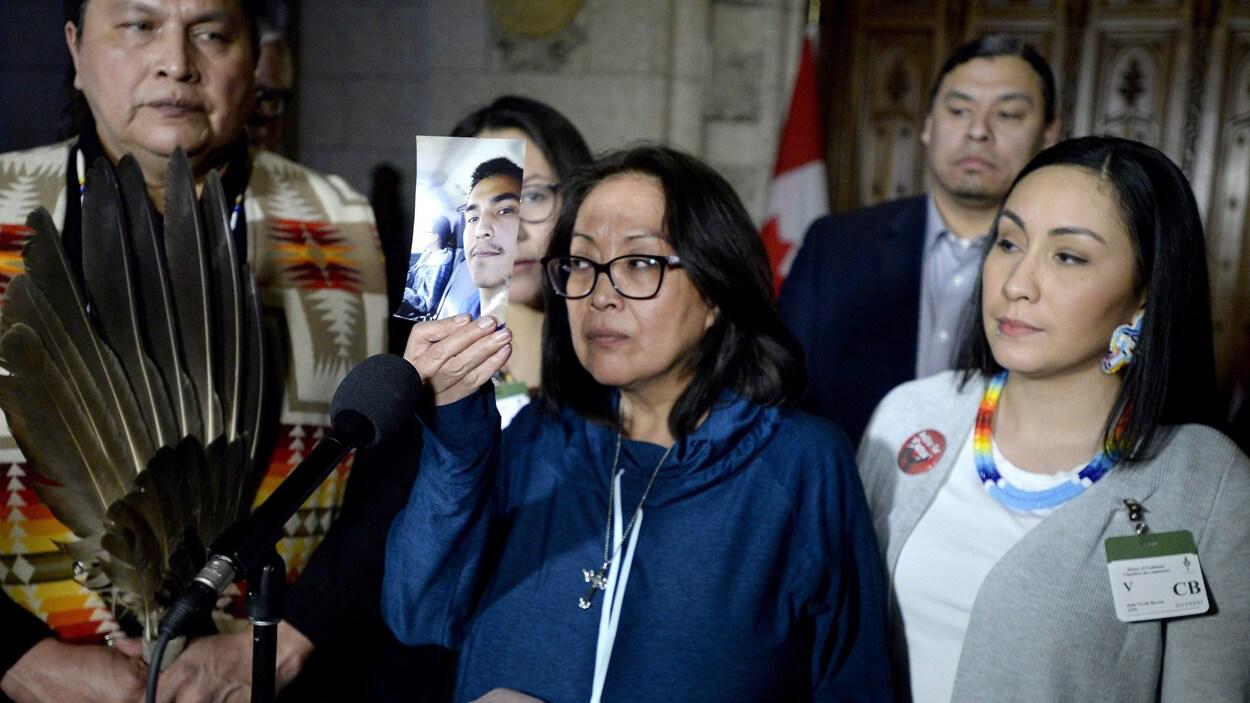 Une femme tenant dans ses mains une photo est entourée d'un homme avec une plume d'aigle et d'une autre femme.