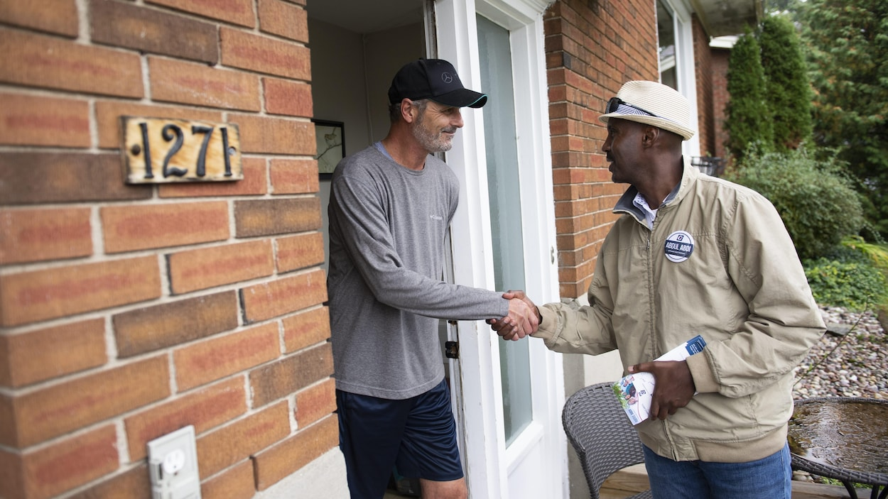 Abdul Abdi, Conservative candidate for Ottawa West-Nepean, shakes hands with a resident as he goes campaigning door to door in Ottawa on Saturday, Sept. 28, 2019. THE CANADIAN PRESS/Justin Tang