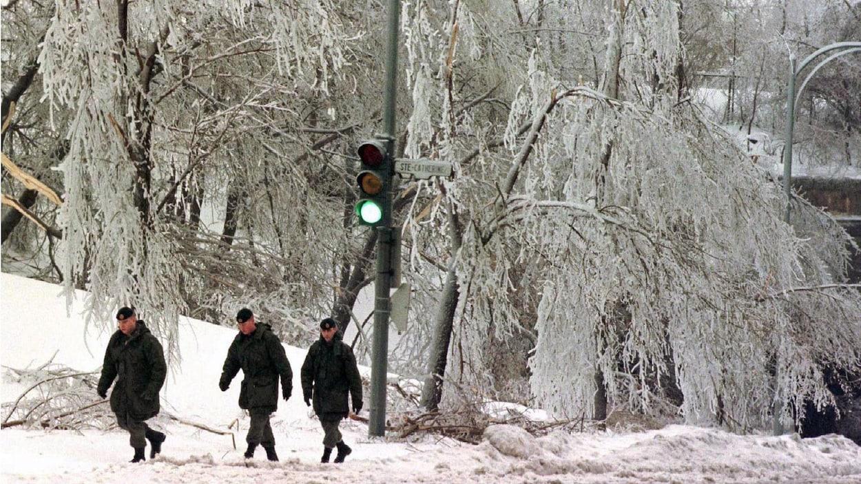 Trois militaires remontent une rue qui borde un parc où des branches d'arbres ploient sous le poids du verglas.