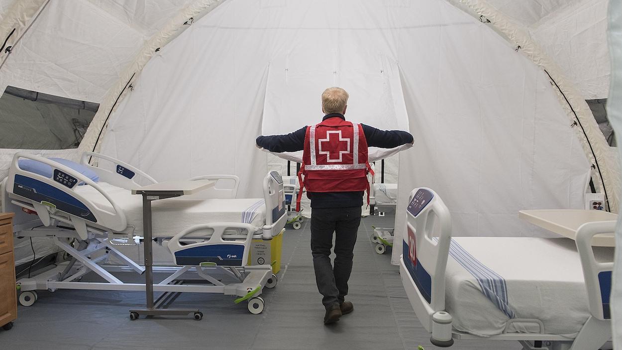 Un employé de la Croix-Rouge vu de dos dans une chambre avec deux lits.