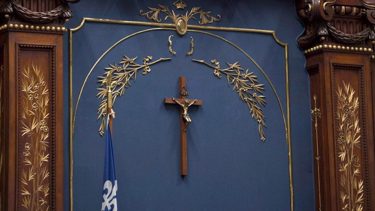 Une croix de bois sous des éléments décoratifs dorés.