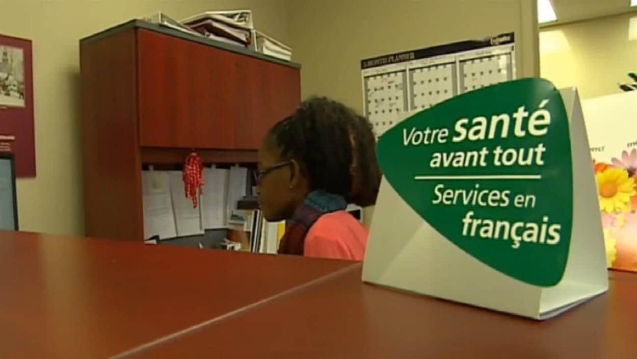 Une affiche posée sur un comptoir de bureau sur lequel il est écrit : « Votre santé avant tout, service en français. »