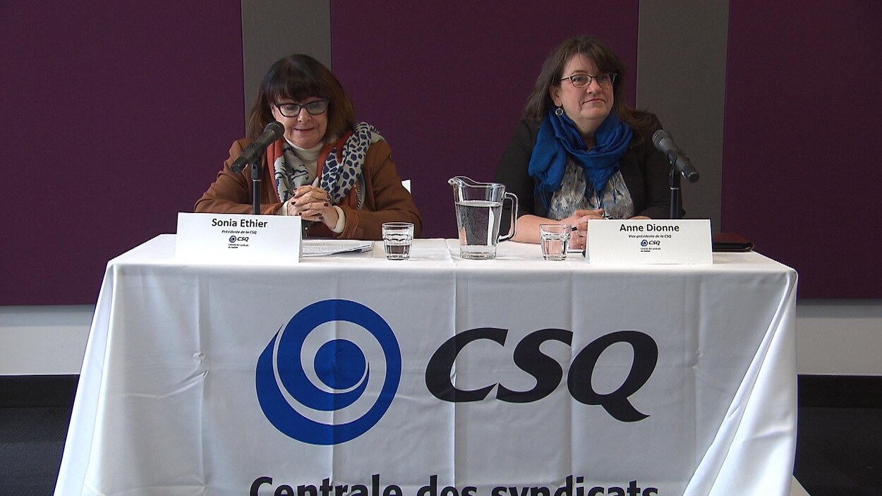 Deux femmes assises à une table s'adressent aux journalistes.