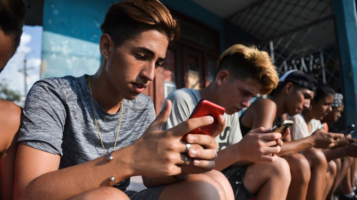 Des garçons regardent leur téléphone mobile assis en rangée.