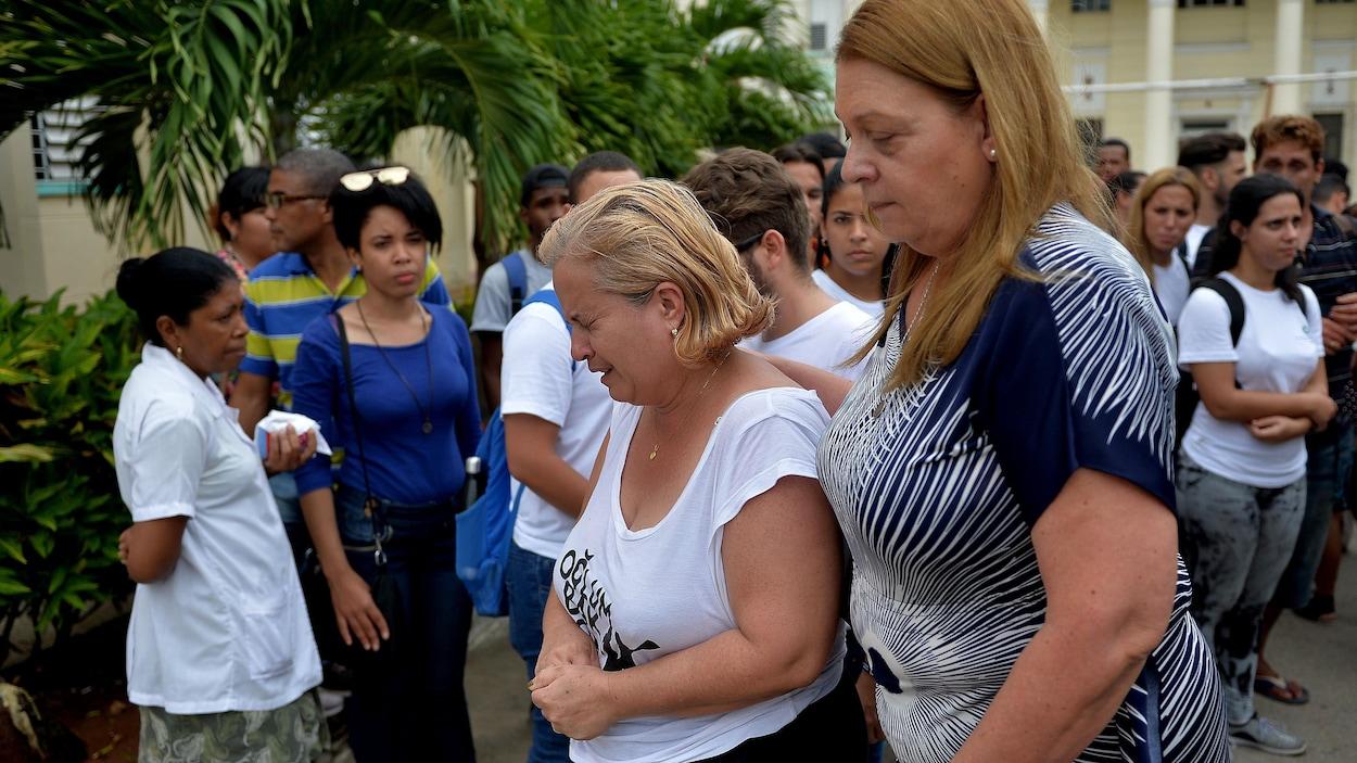 Une femme en pleurs est réconfortée par une autre femme.