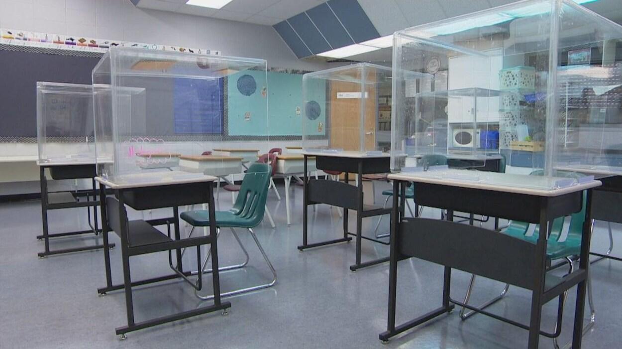 Une salle de classe avec des pupitres surplombés par les cubes de plexiglas.
