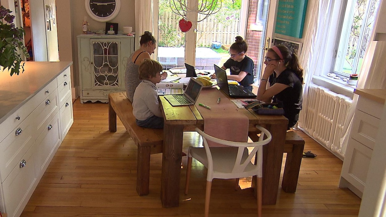 Une mère et ses trois enfants sont assis à la table de la cuisine. Ils suivent tous des cours à distance.