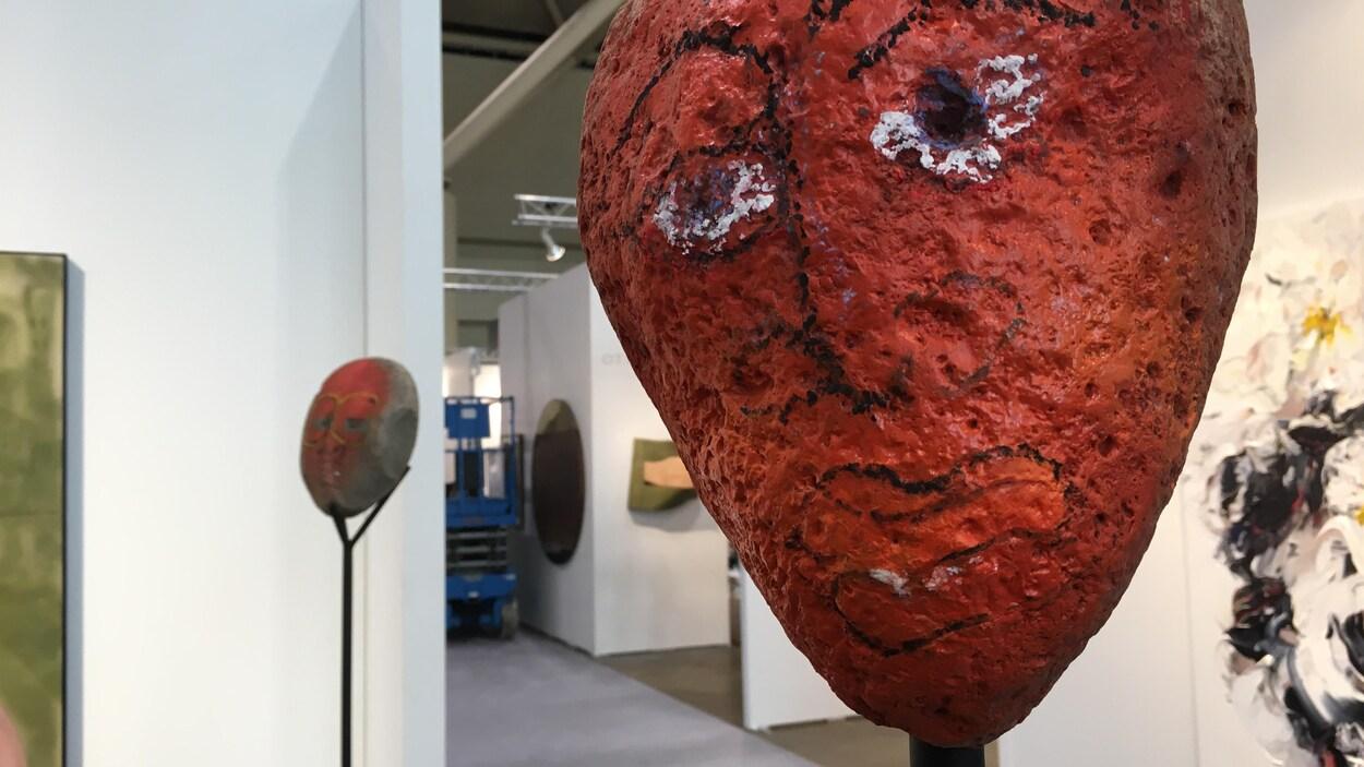 Sculpture qui représente un visage rouge dessiné aux traits noirs avec des yeux blancs