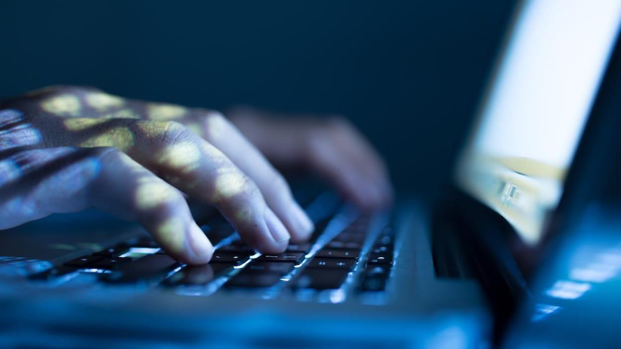 Un homme pose ses mains sur le clavier d'un ordinateur portable dans l'obscurité.
