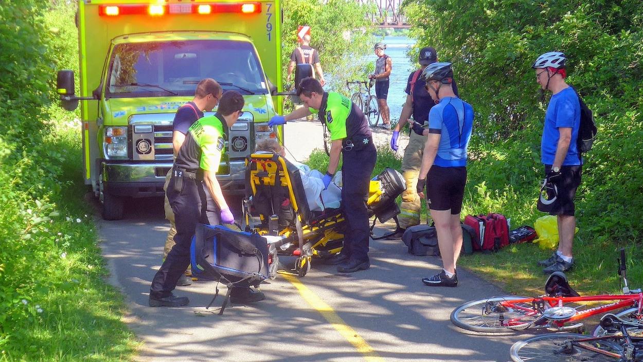 Des ambulanciers paramédicaux interviennent sur une piste cyclable.