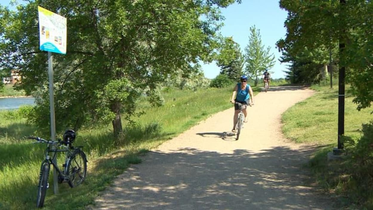 Deux cyclistes sur un sentier en terre battue dans le parc Meewasin à Saskatoon.