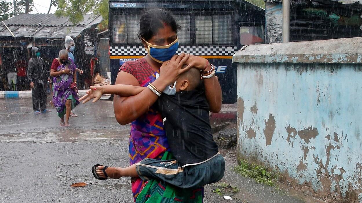 Une Indienne masquée tenant un garçon dans ses bras tente de lui protéger la tête d'une forte pluie avec ses mains.