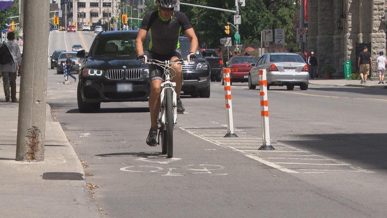 En premier plan, un homme circule à vélo alors qu'un automobiliste s'engage près de la voie cyclable derrière lui.