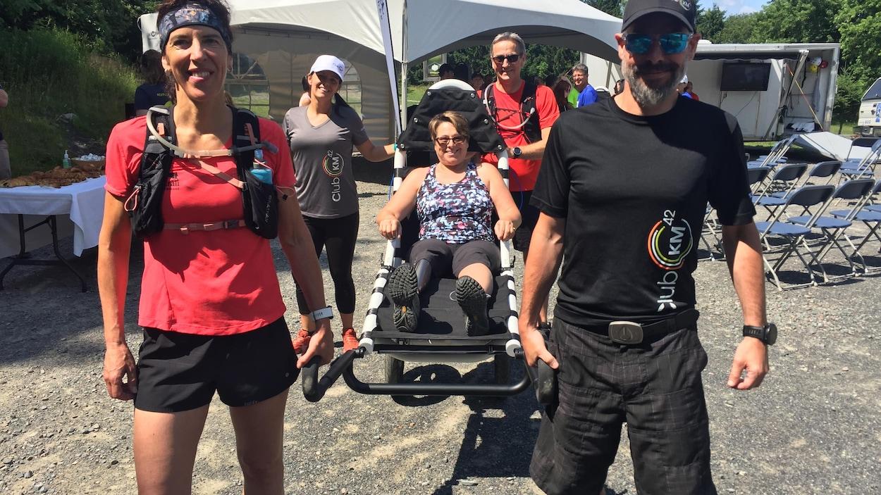 Des bénévoles apportent une personne à mobilité réduite dans un sentier de la montagne.