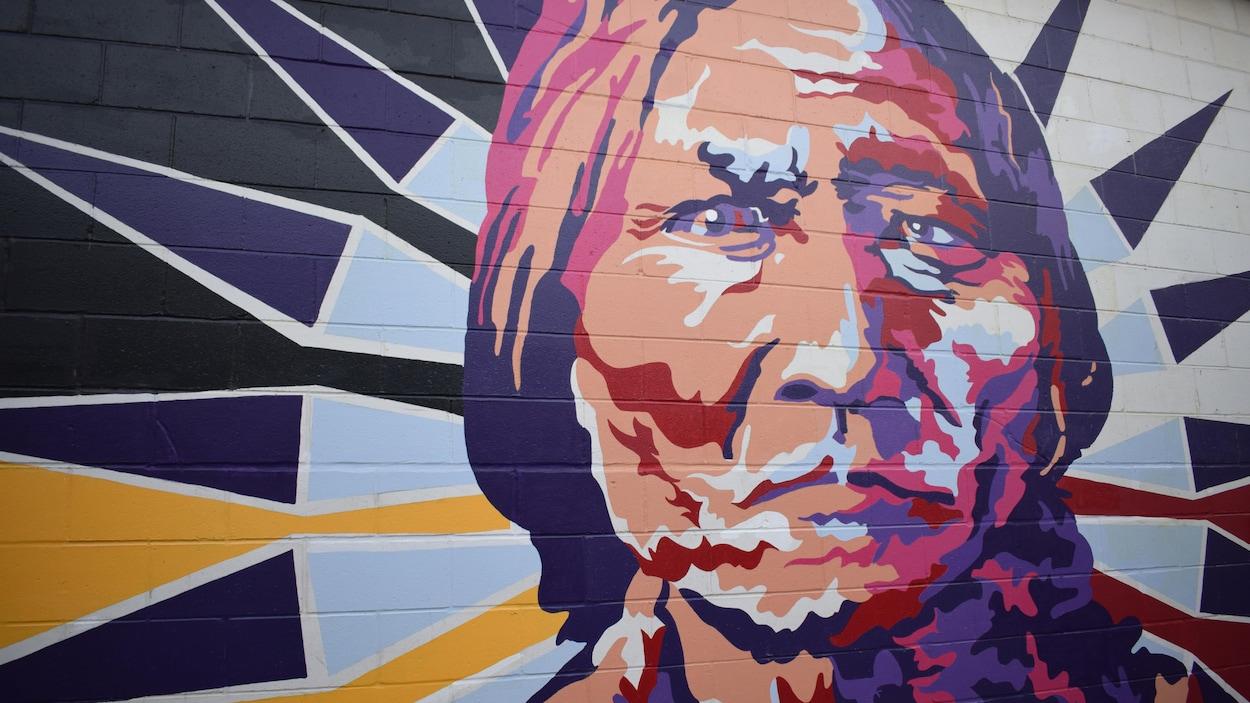 Une fresque colorée représente un chef autochtone fixant droit devant lui.
