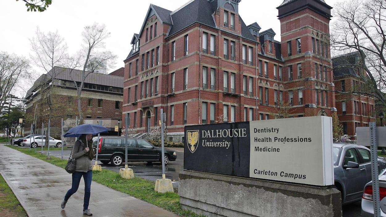 Une passante tenant un parapluie marche devant l'édifice d'une université.