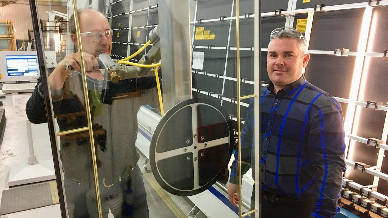 Un homme regarde la caméra en se tenant debout aux côtés d'un ouvrier qui manipule une porte en verre.