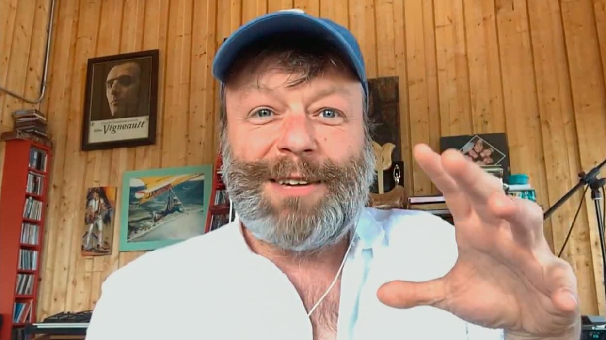 Capture d'écran d'une conversion vidéo avec Daniel Boucher, qui porte une barbe et une casquette bleue.