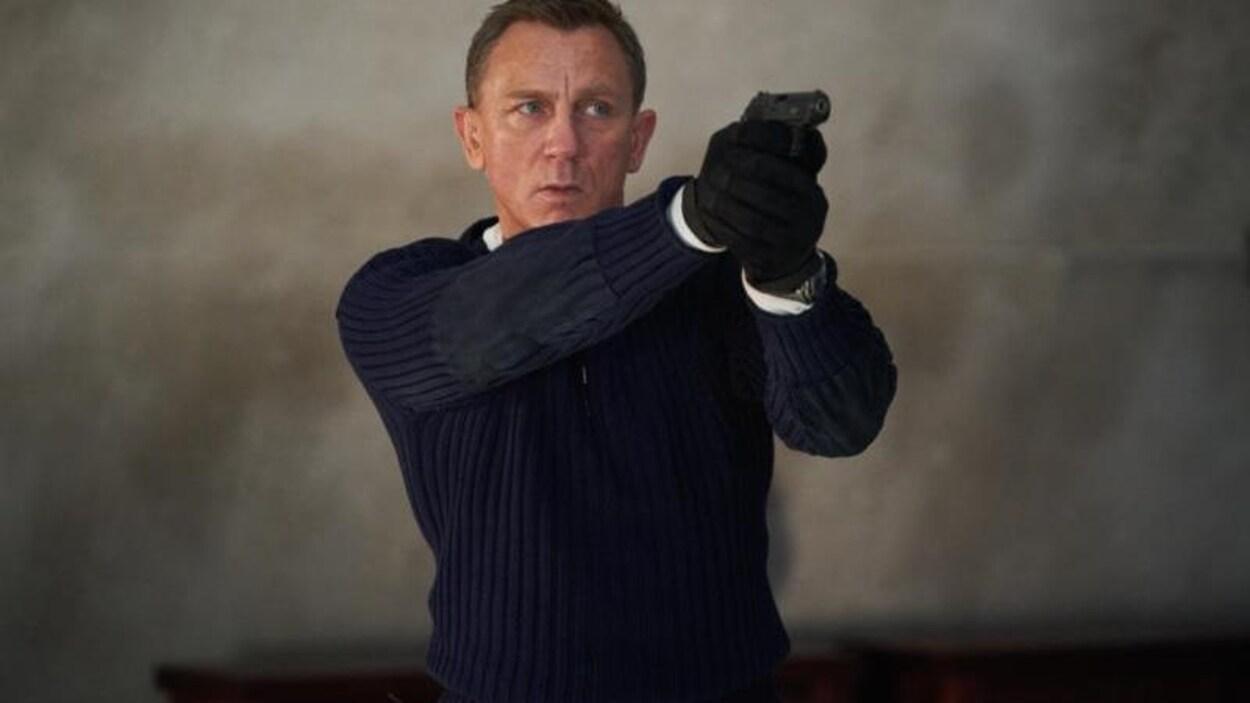 L'homme tient un pistolet et vise.