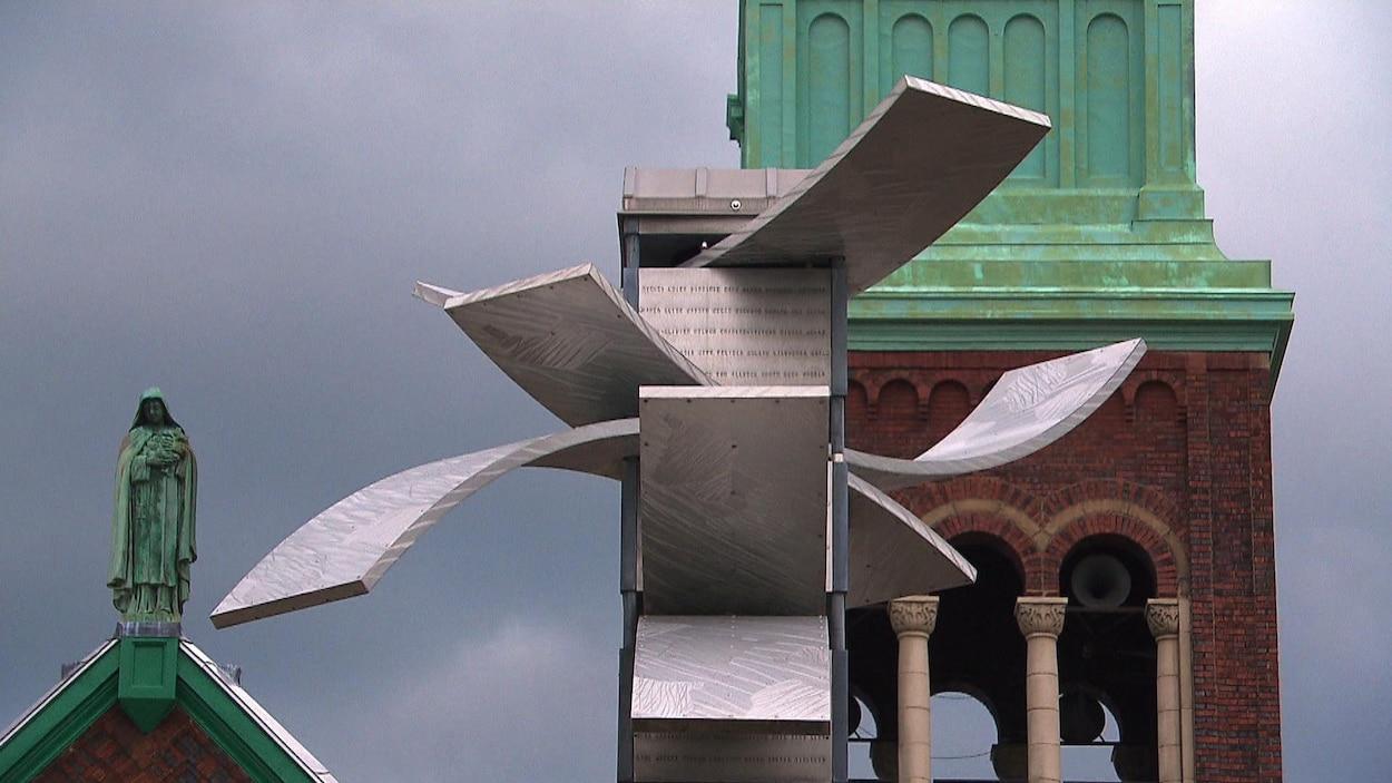 Un gros plan du sommet de l'oeuvre avec le clocher de l'église derrière