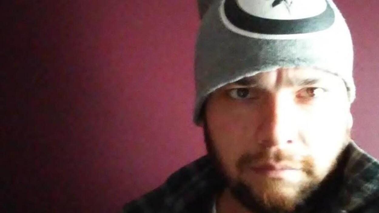 Égoportrait de Daniel Jensen, vu de près. Il porte une tuque et a l'air sérieux.