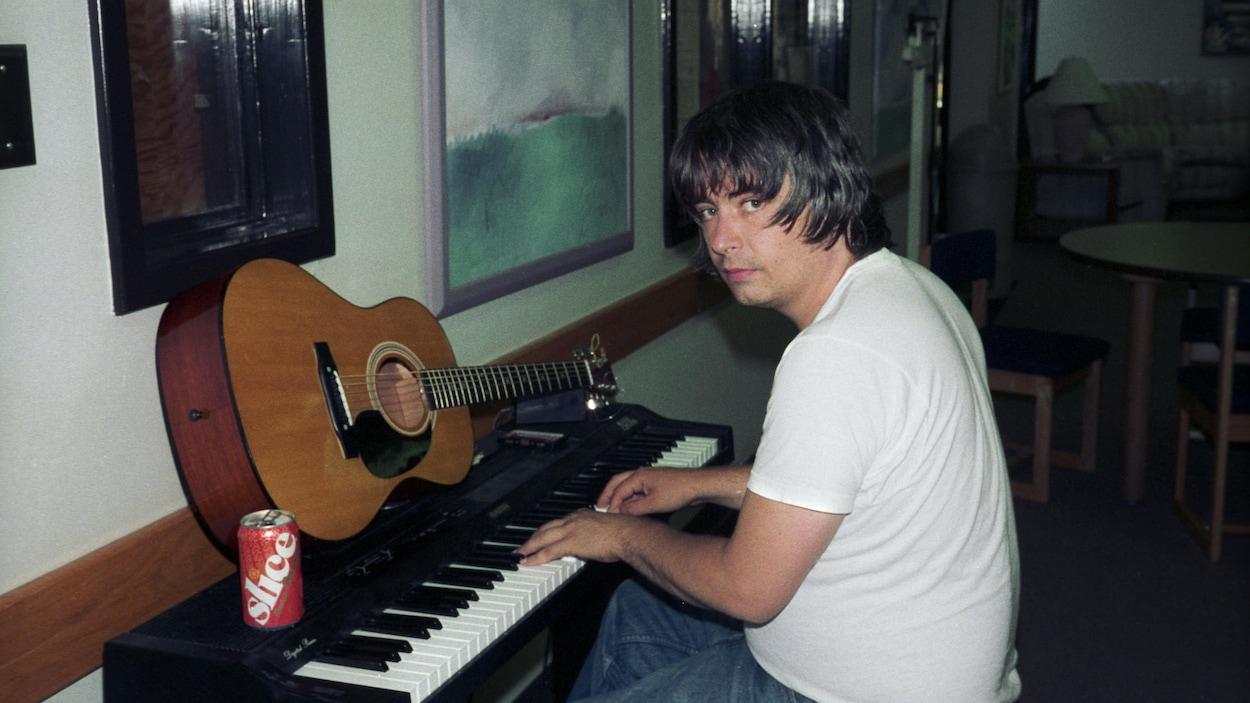 Un homme joue sur un clavier sur lequel une guitare est posée.