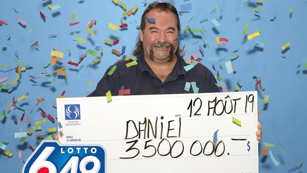 Daniel Lavoie tient un gros chèque de carton indiquant son lot de 3,5 M$.