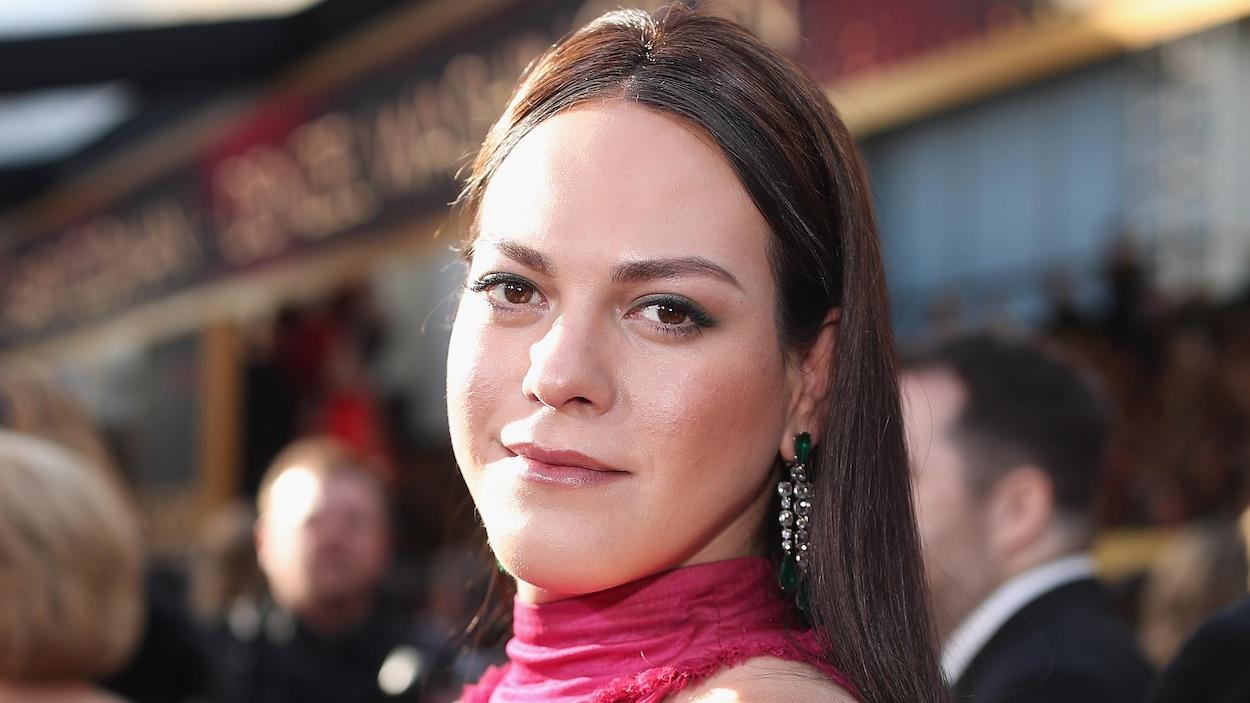 L'actrice chilienne Daniela Vega, vêtue d'une robe rose, regarde la caméra