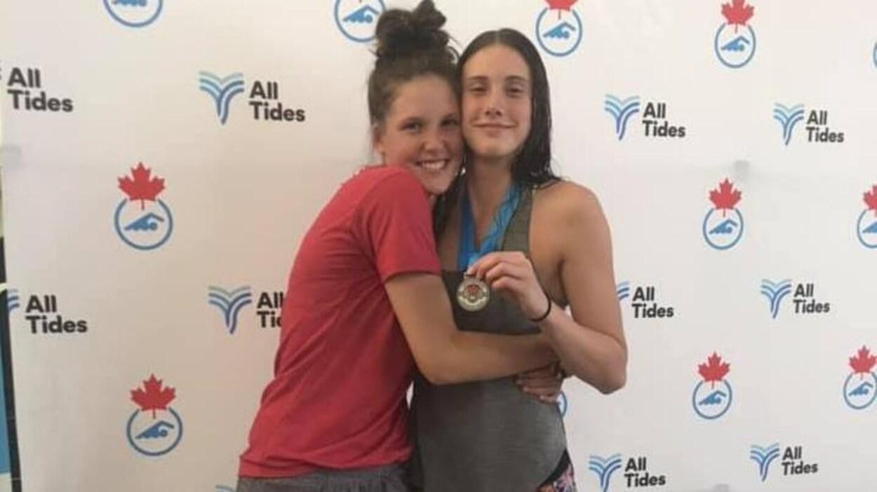 La soeur de Danika, Sarah, fait une accolade à la nageuse qui montre fièrement sa médaille d'argent.