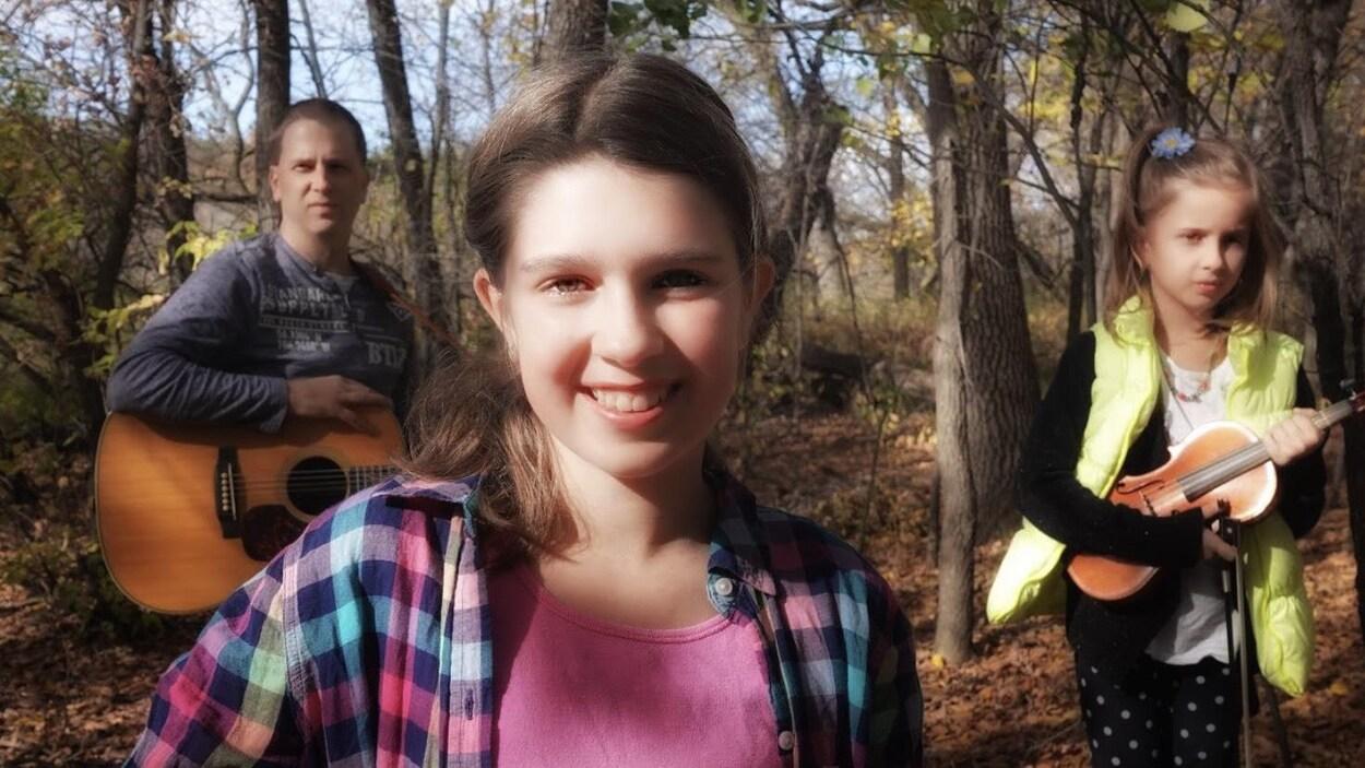 Danika Hutlet pose à l'extérieur avec son père et sa soeur qui sont en arrière-plan.