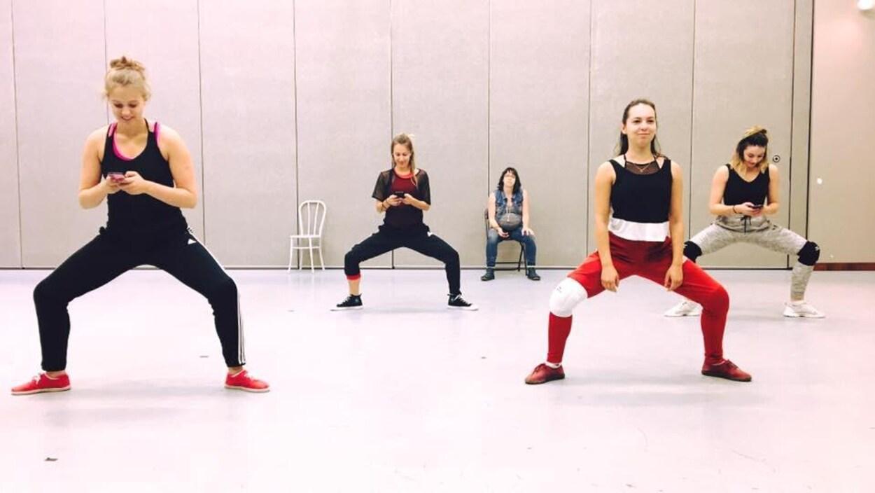 Trois danseuses sont sur leur cellulaire et une autre sourit.